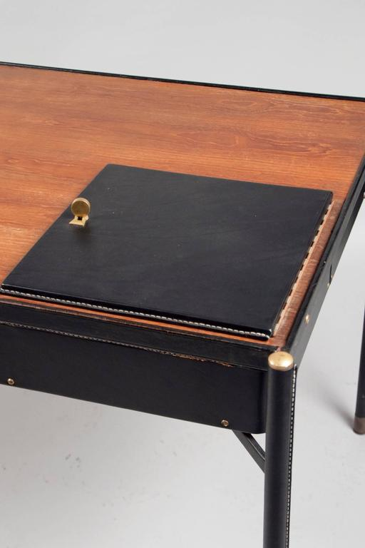 Tubular metal desk covered in black saddle-stitched leather; with an oak work surface containing a lockable leather door, revealing a pivoting compartment underneath.  OUR REFERENCE N9917