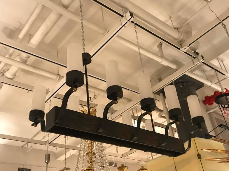 Patinated iron, rectangular structure with ten up-curving arms (five on each side) supporting cylindrical shades of white glass with gilded bronze, spherical finials. The iron body is inset with frosted glass panes for down light and hangs from two