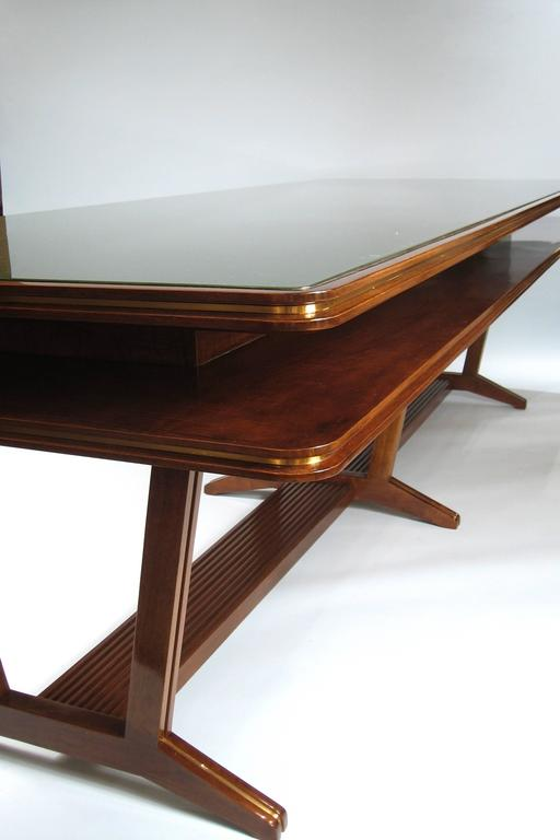 Walnut with brass trim, inset with original dark green glass and under-tier, on three pierced columns, each with two feet, joined by a broad crossbeam.  OUR REFERENCE N3993b