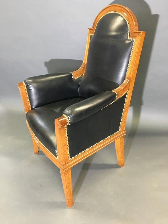 Solid oak upholstered in black leather, with an arched crest rail, upholstered rests and square supports headed with a scroll, atop four tapered and square legs.
