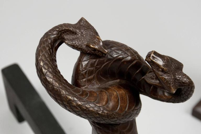 """Pair of cast bronze chenets depicting two intertwined fighting cobras. The iron bars are modern. Each stamped """"E.Brandt.""""  OUR REFERENCE N9587"""