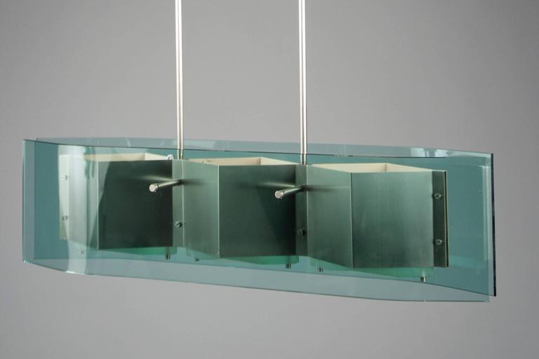 Two metal stems suspending two blue-green curved glass panels encompassing a three-part nickel structure.