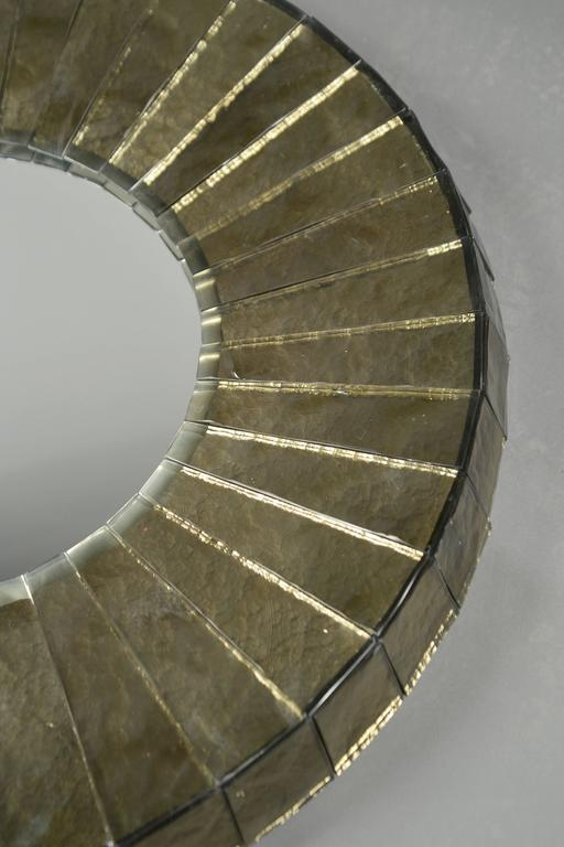 """Hand-hewn wedges of thick mirrored gray glass, abutting similarly chiseled sides, encompassing the round mirrored glass plate. Model """"Leucos"""". The mirror plate itself is 17"""" in diameter."""