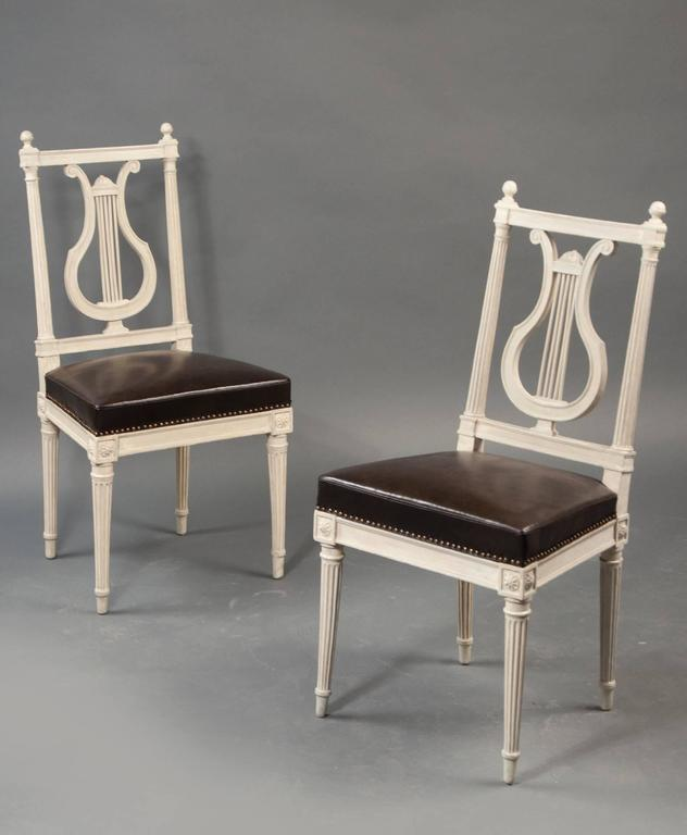 Carved and painted wood with an open lyre-form slat back; over an upholstered, trapezoidal seat; raised on tapered and fluted legs headed with rosettes.