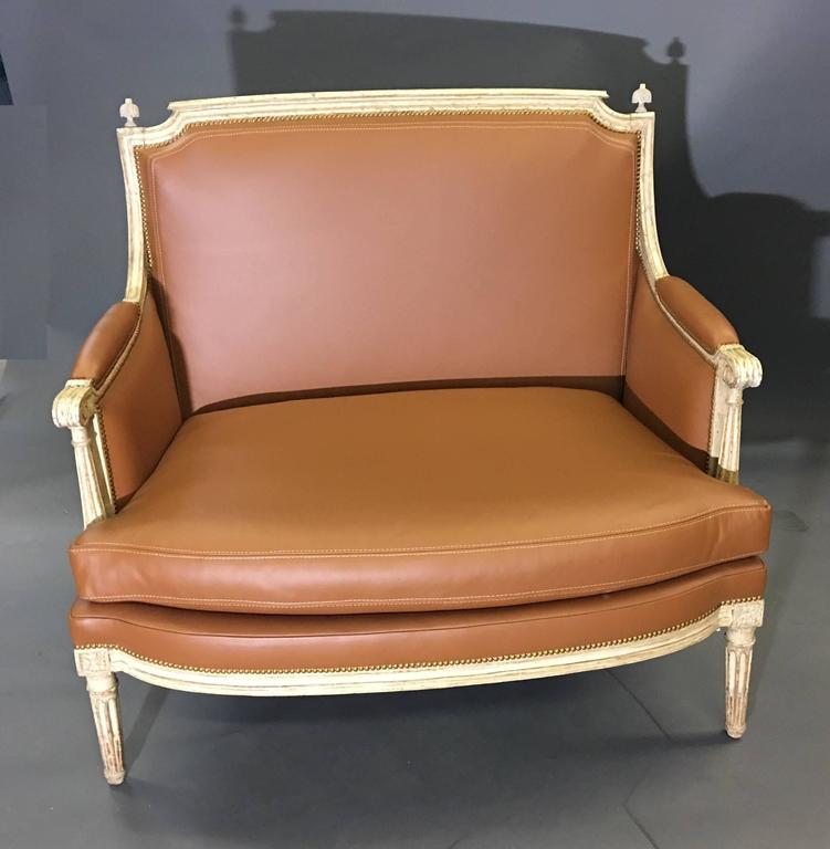 Carved and off-white lacquered wood, upholstered with a cushion seat; the rectangular back connects to padded armrests, ending in scrolls, above curved and fluted supports, raised on tapered and fluted legs headed with rosettes. Partial stamp