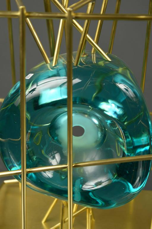 Each lamp composed of a solid brass base supporting a rectangular structure of brass rods, encasing a suspended green, pierced glass disc.