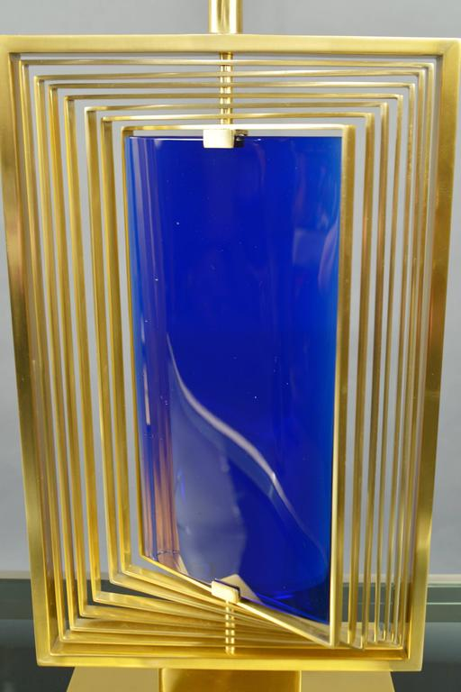 """Model """"Giroscopio"""". Each lamp with rectangular bronze frames of varying sizes mounted to a central stem, which swivel around a sapphire blue glass panel in the center. Measures: Height 31"""