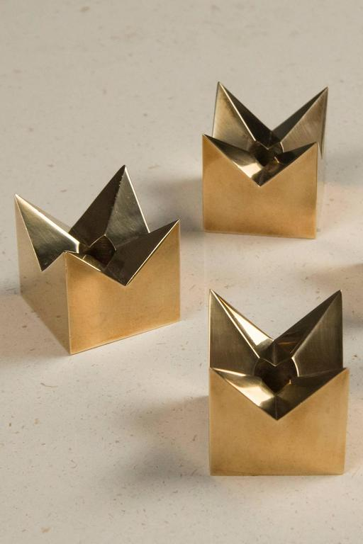 Star-shaped candleholders in brass, each impressed with the maker's mark underneath.