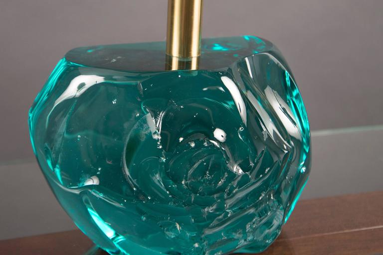 """Hand-hewn blocks of hefty translucent blue-green glass, set with brass shafts, supporting conical white glass shades. Glass Blocks approx. measures: Height 7"""", width 9.5"""", depth 5.25""""."""
