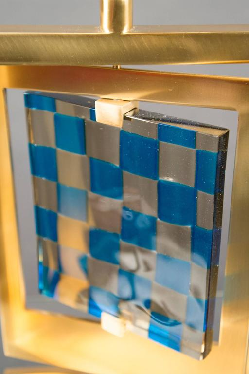 """Model """"Giroscopio"""". Each lamp with a rectangular brass frame mounted to a central stem, which swivels around a blue and gray checkered vintage glass panel, produced by Venini."""