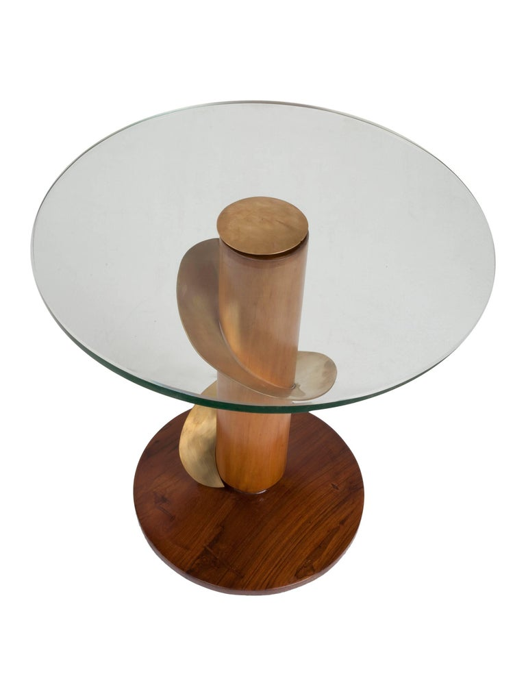 Teak and brass side tables with a swirl of brass around the stem and glass tops. Glass piece can be removed by taking off the brass center piece. Diameter of the base is 12 inches. Mid-Century Modern.