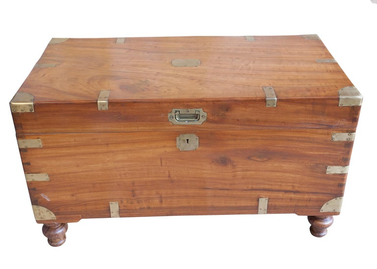 Classic British campaign camphor wood sea chest. Brass straps and handles, recessed brass pull and escutcheon with working lock and key. Feet were added to accommodate use as a coffee table (keeps your feet from hitting the box). Still has its