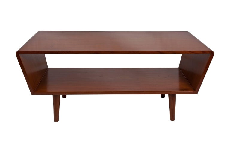 Danish, Mid-Century Modern teak wood coffee or cocktail table with great clean-lined style Storage on lower shelf, tapered legs and slanted sides, circa 1950s-1960s. Height of lower shelf is 10 inches.  Mid-Century Modern and Art Deco pieces on