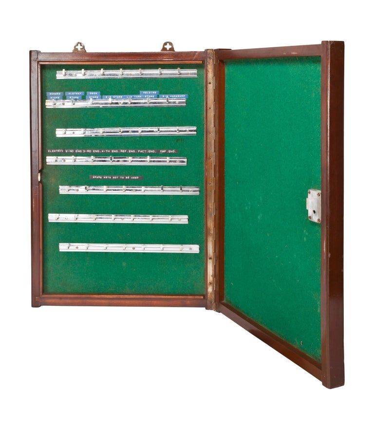 A teak key storage cabinet lined with green felt and chrome hooks. The front door closes and locks. From a decommissioned ship, circa 1970s. A rare find. Complete with lock and key and mounting brackets and the original embossed key labels.