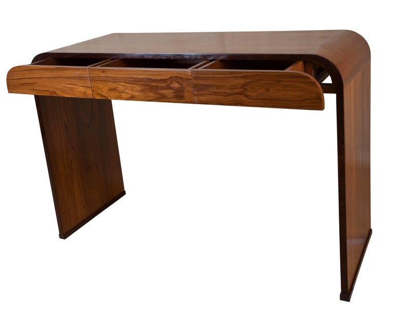 Mid-Century Modern 'waterfall' desk made of teak with rosewood borders. Three front drawers, the two on the sides have rounded corners. Refinished. Great to use as a desk, console or sofa table. Elegant lines and lovely wood grain. Height from the