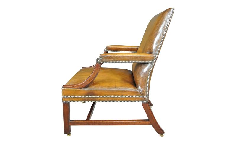 George III mahogany Gainsborough chair of large proportions raised on chamfered legs, recently reupholstered in a close buttoned antiqued hide Provenance Hinton house excellent condition.