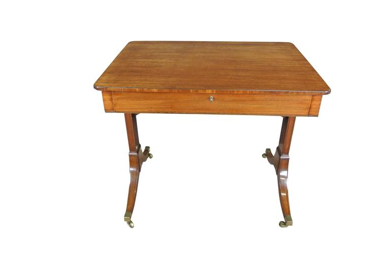 A fine Regency mahogany and inlaid ebony single drawer occasional table with Re-entrant corners and end supports on outswept feet ending in brass castors.