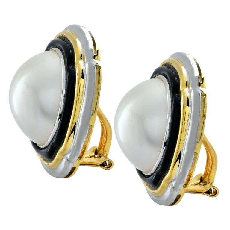 Beautiful platinum and 18K yellow gold earrings featuring Mabe pearls measuring 17mm in diameter. The pearls are framed in enamel, 18K yellow gold and platinum. These attractive earrings measure 1.04 inches by 1.04 inches in diameter. They currently