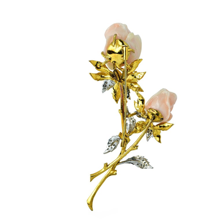 Beautiful brooch pin crafted in 18K yellow gold showcasing two rosebuds finely crafted in dainty pink angel skin coral, with leaves adorned with 38 round brilliant cut diamonds weighing .40 carats. This brooch measures 3.5 inches in length and 2.1