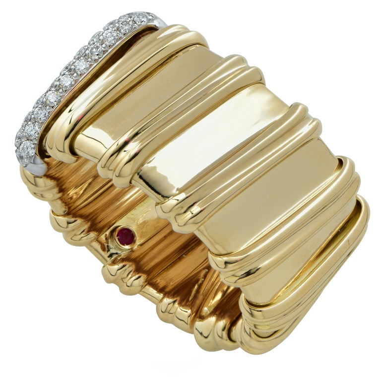 Stunning Roberto Coin Flexible band crafted in 18K yellow gold featuring twelve gold double line accents, one of which is adorned with 31 round brilliant cut diamonds weighing approximately .21 carats total weight, in a pave' setting. Featuring the
