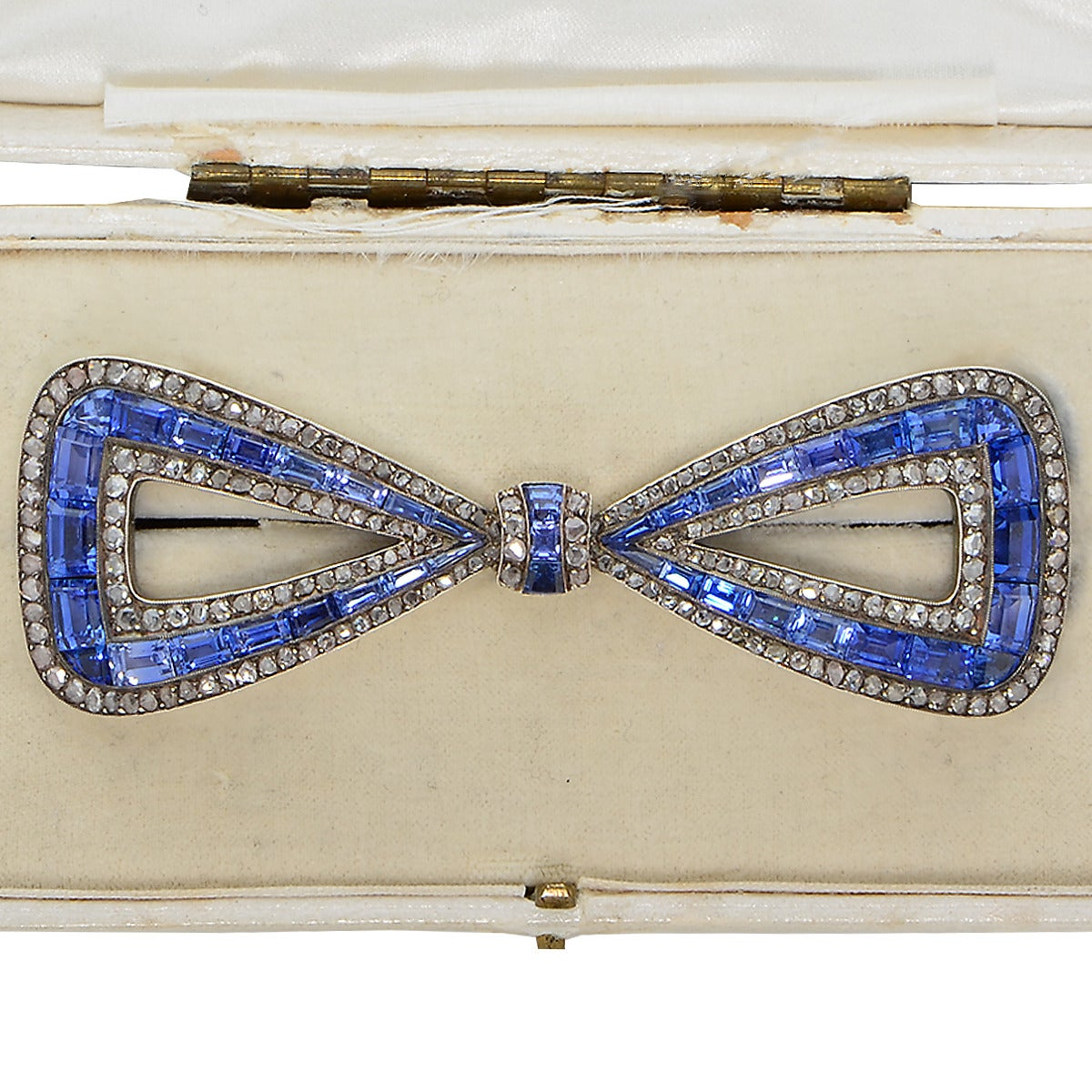 This delightful antique 18k yellow gold and silver bow tie pin with original box features 41 natural blue sapphires weighing approximately 30.00cts surrounded by 208 rose cut diamonds weighing approximately 5.00cts.  The brooch/pin measures 1.25