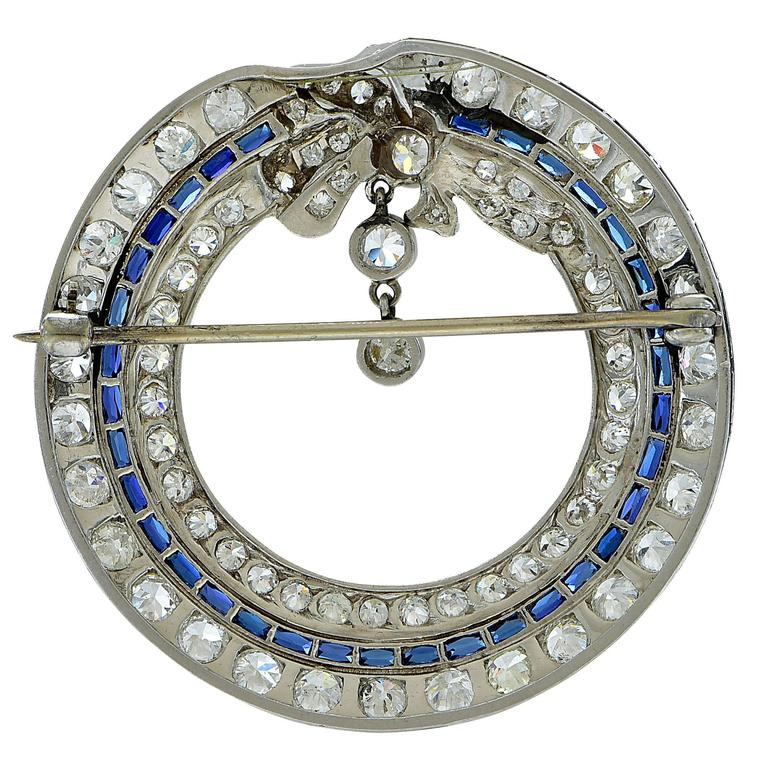 This artistically crafted platinum Art Deco brooch features 78 European cut diamonds weighing approximately 4.25cts  F-G color, VS clarity and is accented by 34 scissor cut synthetic sapphires, typical of the Art Deco period.  The brooch measures
