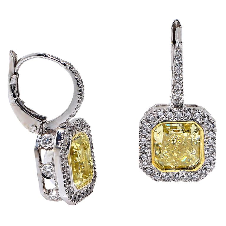 2.02 Carat Fancy Light Yellow, VS2 Clarity, GIA Graded Radiant Cut Diamond Matched with a 1.73 Carat Fancy Yellow, VS2 Clarity, GIA Graded Radiant Cut Diamond Surrounded by 70 Round Brilliant Cut Diamonds Weighing .85 Carats, F Color, VS Clarity,