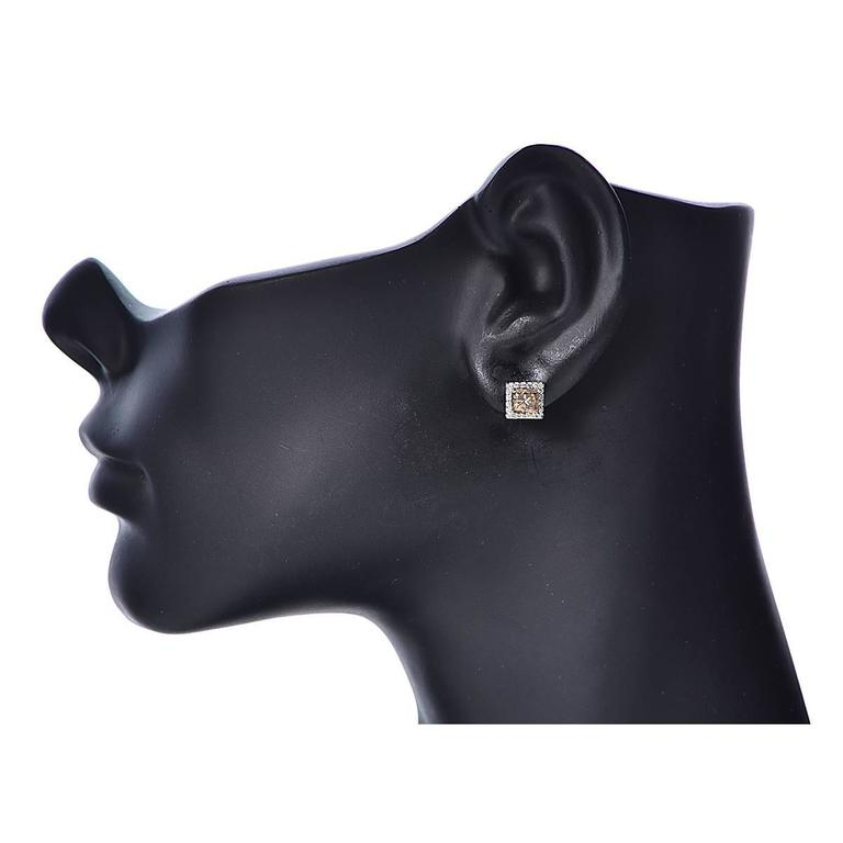 18 Karat White Gold Stud Earrings Featuring 2 Natural Fancy Brown Princess Cut Diamonds Weighing Approximately 2.02 Carats Accented by 40 Round Brilliant Cut Diamonds Weighing Approximately .26 Carats, G Color, SI Clarity.  Weight: 3.74