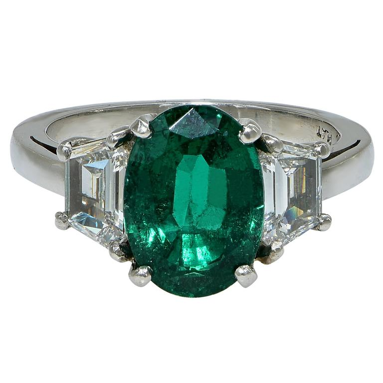 Beautiful rich green AGL graded 2.75ct oval cut emerald flanked by two trapezoid cut diamonds set in a modern platinum engagement ring.  The ring is a size 6.5 and can be sized up or down. Measurements are available upon request. It is stamped