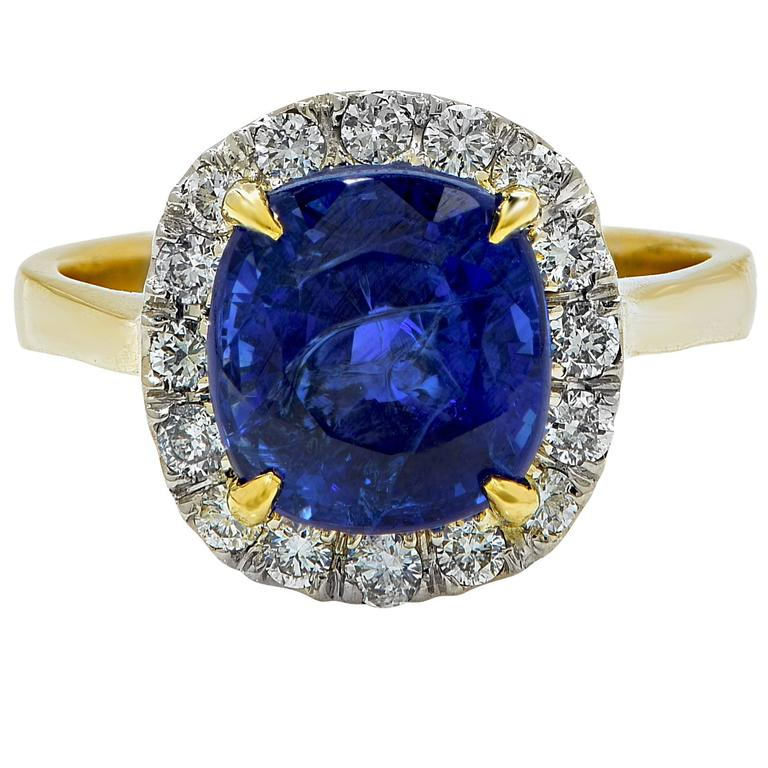 AGL graded 4.97ct vibrant heated blue sapphire from Madagascar set in to an 18k yellow gold ring and surrounded by 16 round brilliant cut diamonds G-H color and SI1 clarity.  The ring is a size 6 and can be sized up or down. It is stamped and tested