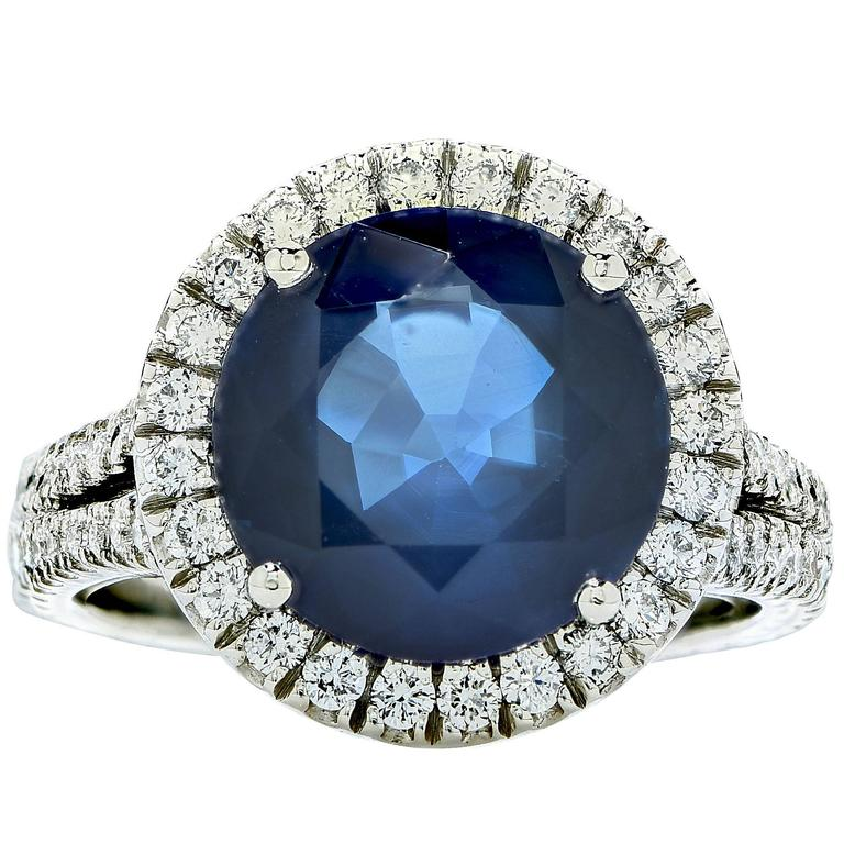 This beautiful platinum custom-made ring features a 5.93ct round cut sapphire surrounded  by .84cts of round brilliant cut diamonds, G color, VS clarity.  The ring is a size 6 and can be sized up or down. It is stamped and tested as platinum. The