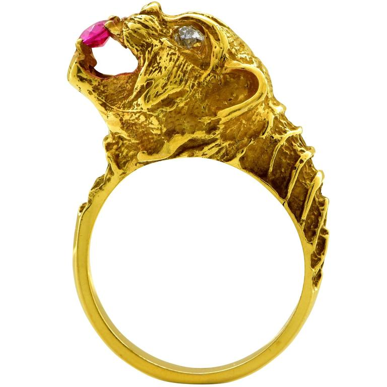 18k yellow gold Lion ring featuring a round cut synthetic ruby weighing approximately .15cts accented by 2 European cut diamonds weighing approximately .20cts total, G color SI clarity.  The ring is a size 7 and can be sized up or down. It is