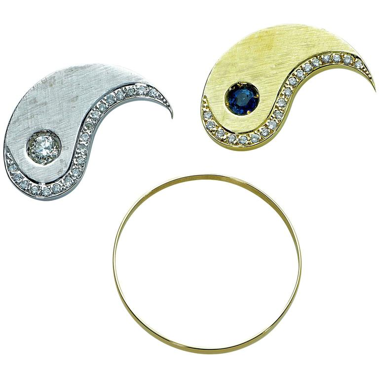 18k white and yellow gold ying-yang pendant featuring a round cut sapphire weighing approximately .40cts and a round brilliant cut diamonds weighing approximately .35cts G color VS clarity accented by 34 round brilliant cut diamonds weighing