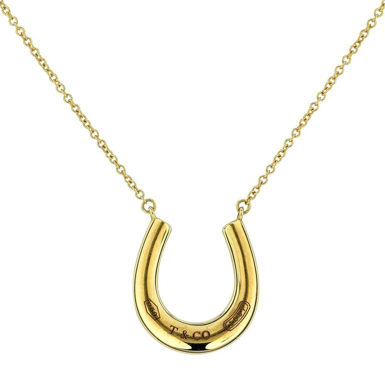 Tiffany & Co. 1837 horseshoe pendant and necklace crafted in 18k yellow gold.  The pendant measures 0.61 inch in width by 0.61 inch in height and is strung from an 18 inch chain. It is stamped and/or tested as 18k gold. This pendant weighs 3.74