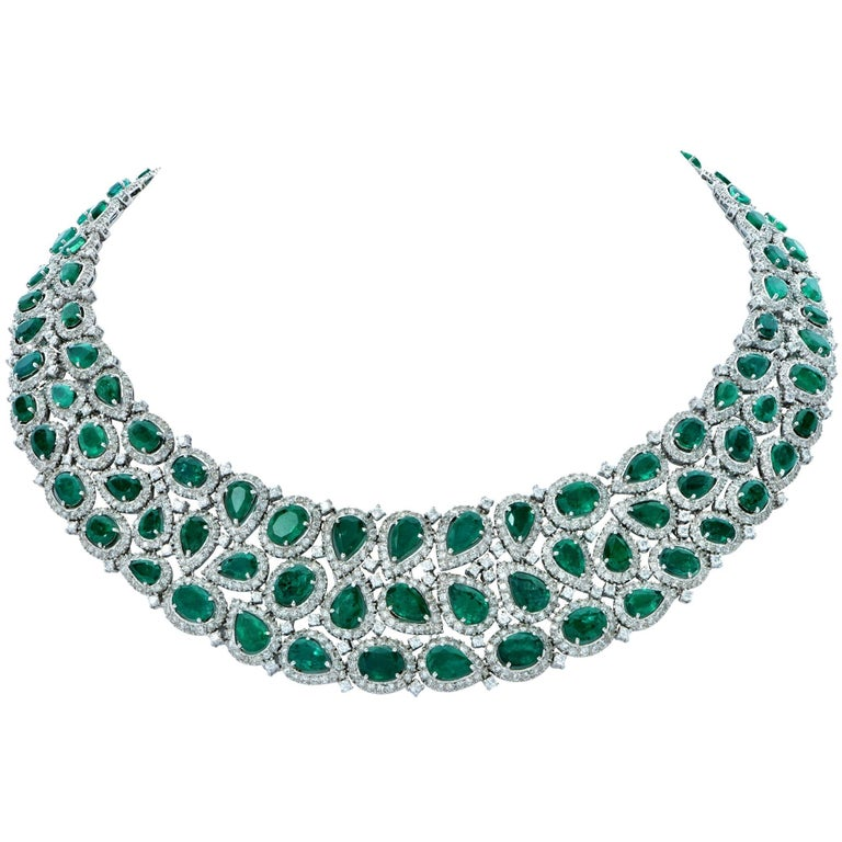 Spectacular rich green emerald and diamond necklace and earrings set crafted in 18k white gold. This elegant set boasts an impressive total approximate weight of 101 carats of oval and pear shape emeralds set in a sea of white round brilliant cut