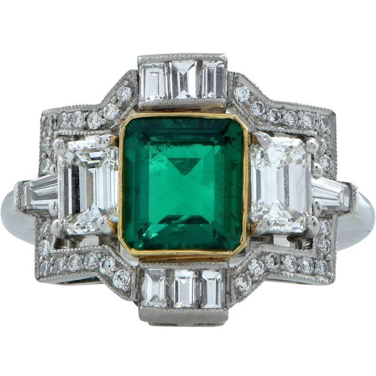 Platinum and 18k yellow gold ring featuring an emerald cut emerald from Colombia weighing approximately 1.50cts. Flanked by 2 emerald cut diamonds weighing 1ct total, G color VS clarity, accented by approximately .55cts total G color VS