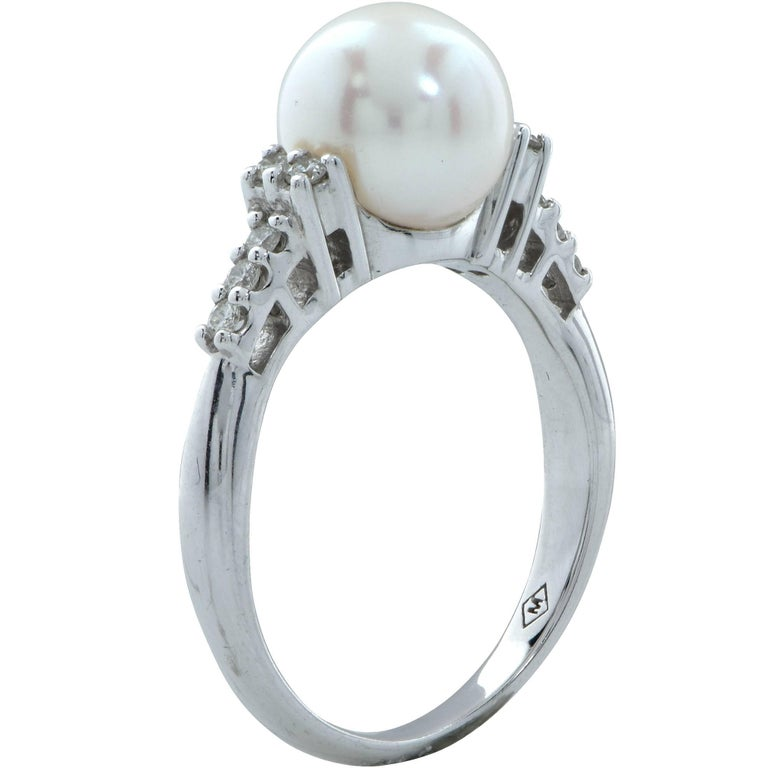 14k white gold ring featuring a 8.6mm pearl accented by 10 round brilliant cut diamonds weighing approximately .20cts total, G color VS clarity.  The ring is a size 7 and can be sized up or down. Measurements are available upon request. It is