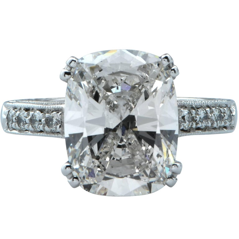 This stunning platinum engagement ring features a GIA graded 5.10ct cushion cut diamond, I color, SI1 clarity, and has very good polish and symmetry. It is accented by .85ct of round brilliant cut diamonds, G color, VS clarity. Its total diamond