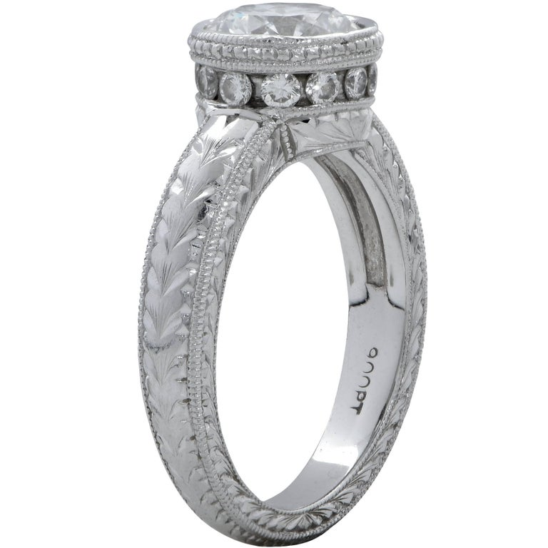 Platinum engagement ring containing a GIA graded 1.11ct, G color, VS2 clarity, round brilliant cut diamond. This ring is hand etched and engraved, and is also accented by 12 round brilliant cut diamonds weighing approximately .20cts.  The ring is a