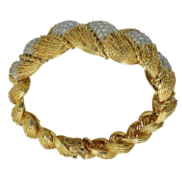 Gorgeous 18k yellow gold and platinum Hammerman Brothers bracelet featuring 147 round brilliant cut diamonds weighing approximately 6.5cts total H color Vs clarity. This finely crafted bracelet is rich in texture and enveloping layers, with twists
