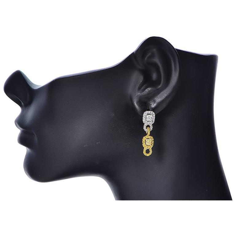 Platinum and Gold Diamond Earrings Featuring 2 Fancy Yellow Radiant Cut Diamonds with an Estimated Total Weight of .66cts and Two Emerald Cut Diamonds, G Color, with an Estimated Total of .80cts Surrounded by 100 Round Brilliant Cut Diamonds White