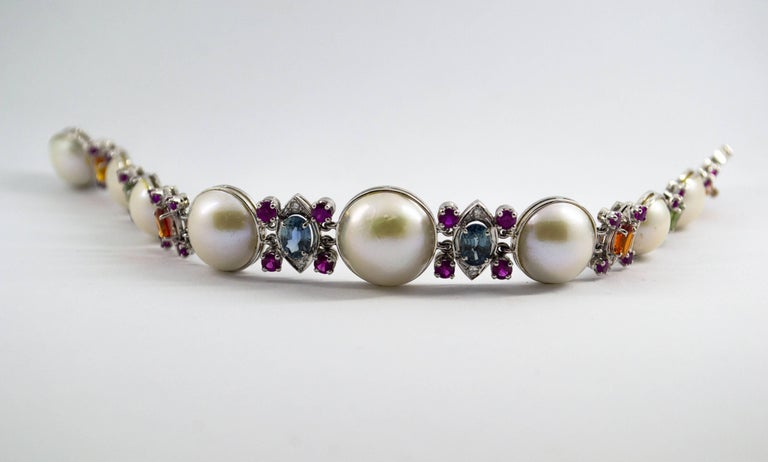 This Bracelet is made of 14k White Gold. This Bracelet has 0.30 Carats of Diamonds. This Bracelet has 10.0 Carats of Rubies and Colored Sapphires (Green, Blue and Yellow). This Bracelet has also Mabe Pearls. We're a workshop so every piece is