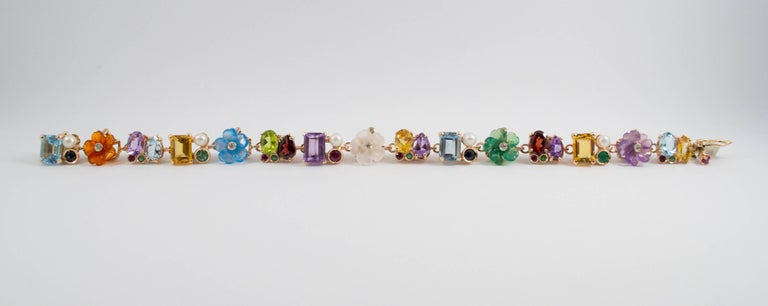 This bracelet is made of 14K Yellow Gold.  This bracelet has 0.20 Carats of White Diamonds. This bracelet has 0.80 Carats of Rubies, Emeralds and Blue Sapphires. This bracelet has also Rock Crystal, Agate, Carnelian, Pearl, Peridot, Amethyst,