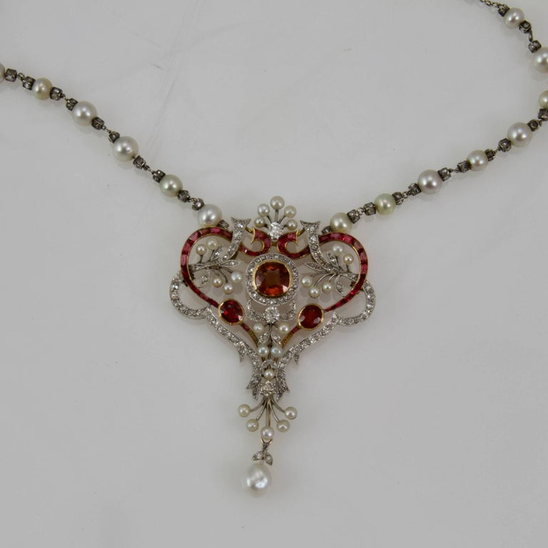 Pendent and its chain typically of Belle Epoque Period.  Designed with heart and leaves pattern interlaced.  The main stone is a spinelle red orangy.  Overall set in