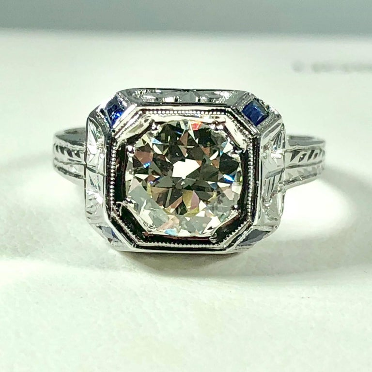 Art Deco 18 karat 1.40 carat European cut diamond and sapphire engagement ring. This true Art Deco piece is a work of art. Created in 18 karat white gold weighing, 3.8grams, 2.4 dwt. Filigree cut out design build up the dome centerpiece. The light