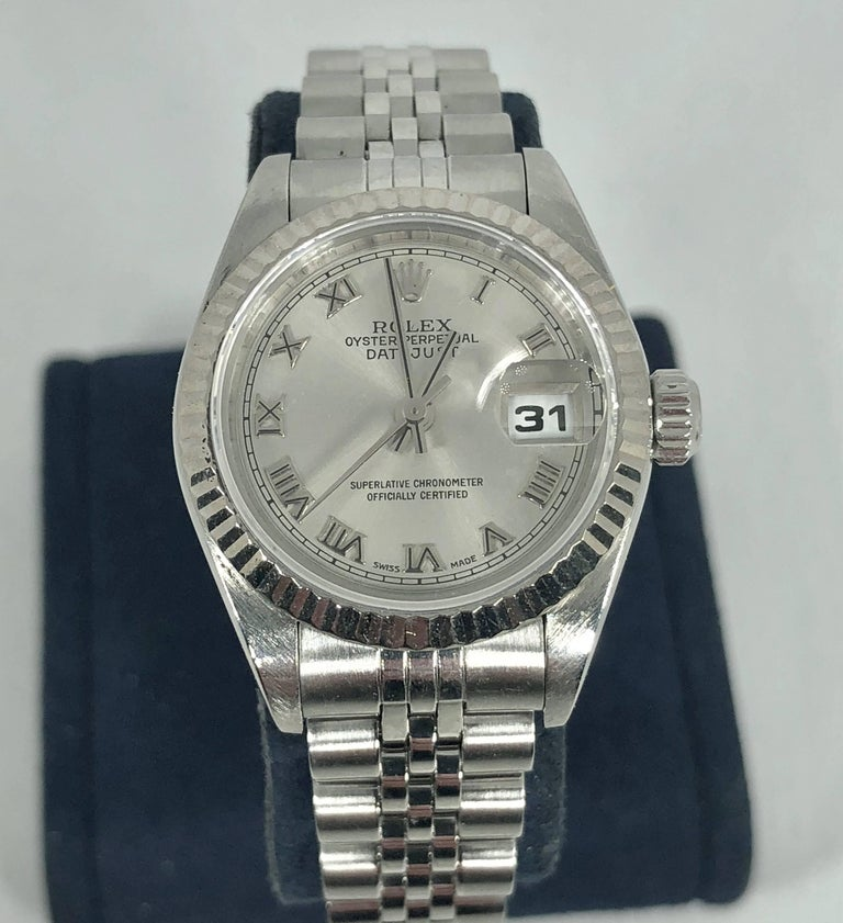 Rolex women's stainless steel and 18 karat Oyster perpetual Datejust wristwatch. Style #79174 serial # A989160. Circa 1999. Stainless steel and 18 karat white gold fluted bezel, 26 MM. Grey dial with roman numerals. Automatic movement with scratch