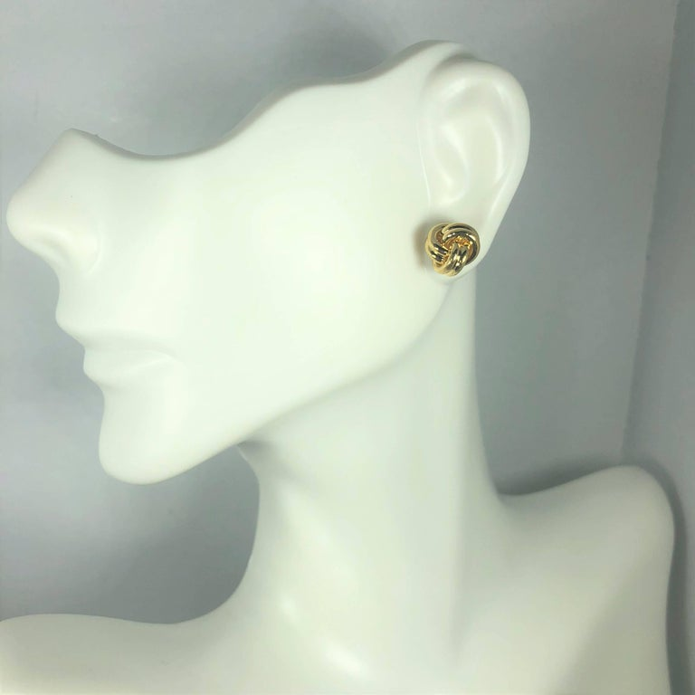 Tiffany & Co. 18 karat yellow gold love knot stud earrings. These classic Tiffany & Co earrings are created in 18 karat yellow gold and weigh 5.4 grams. They are a 3 dimensional knot design, stud earring. Measuring approx. 9mm. Signed on posts