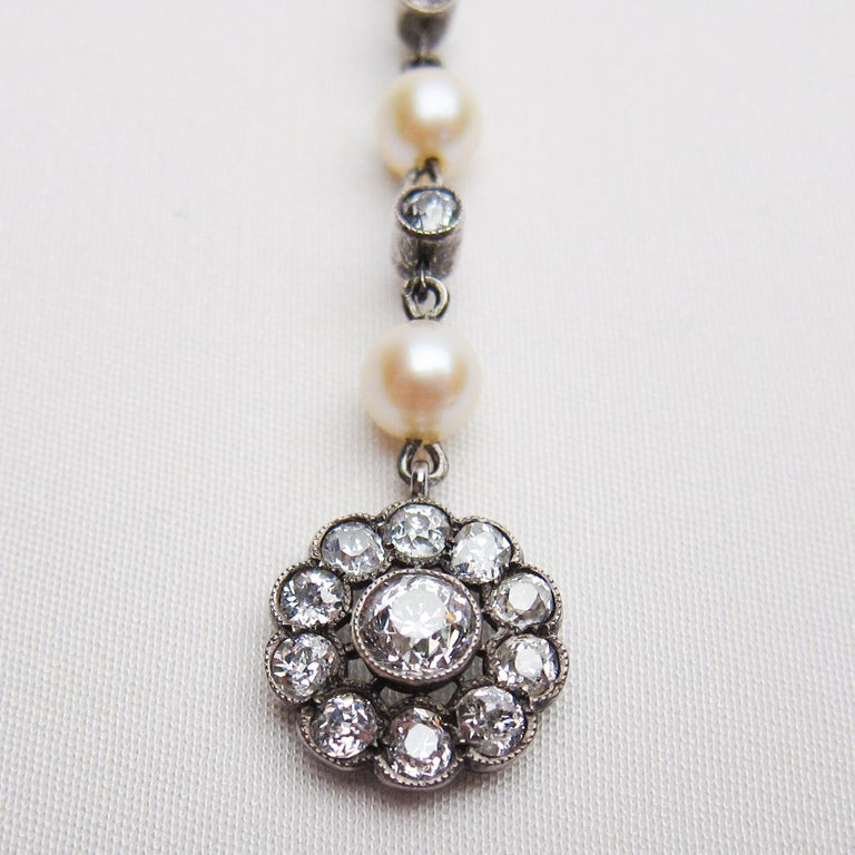 Circa 1910. This stunning Edwardian women's pendant features a cluster setting accented with 11 bezel-set, old European-cut diamonds surmounted by three cultured saltwater pearls, two bezel-set old European-cut diamonds, and 12 bead-set rose-cut