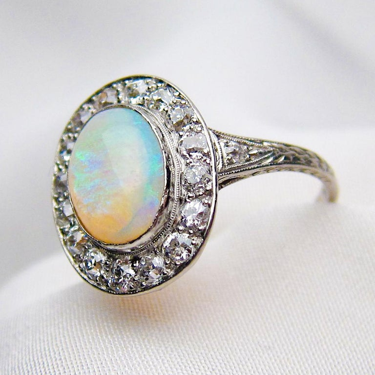 Circa 1920. This lovely Art Deco ring features a cabochon-cut 1.40 carat opal bezel-set in platinum. The opal features a blue and green play of color with a broad flash color pattern and is surrounded by a halo of 16 round old European-cut diamonds.