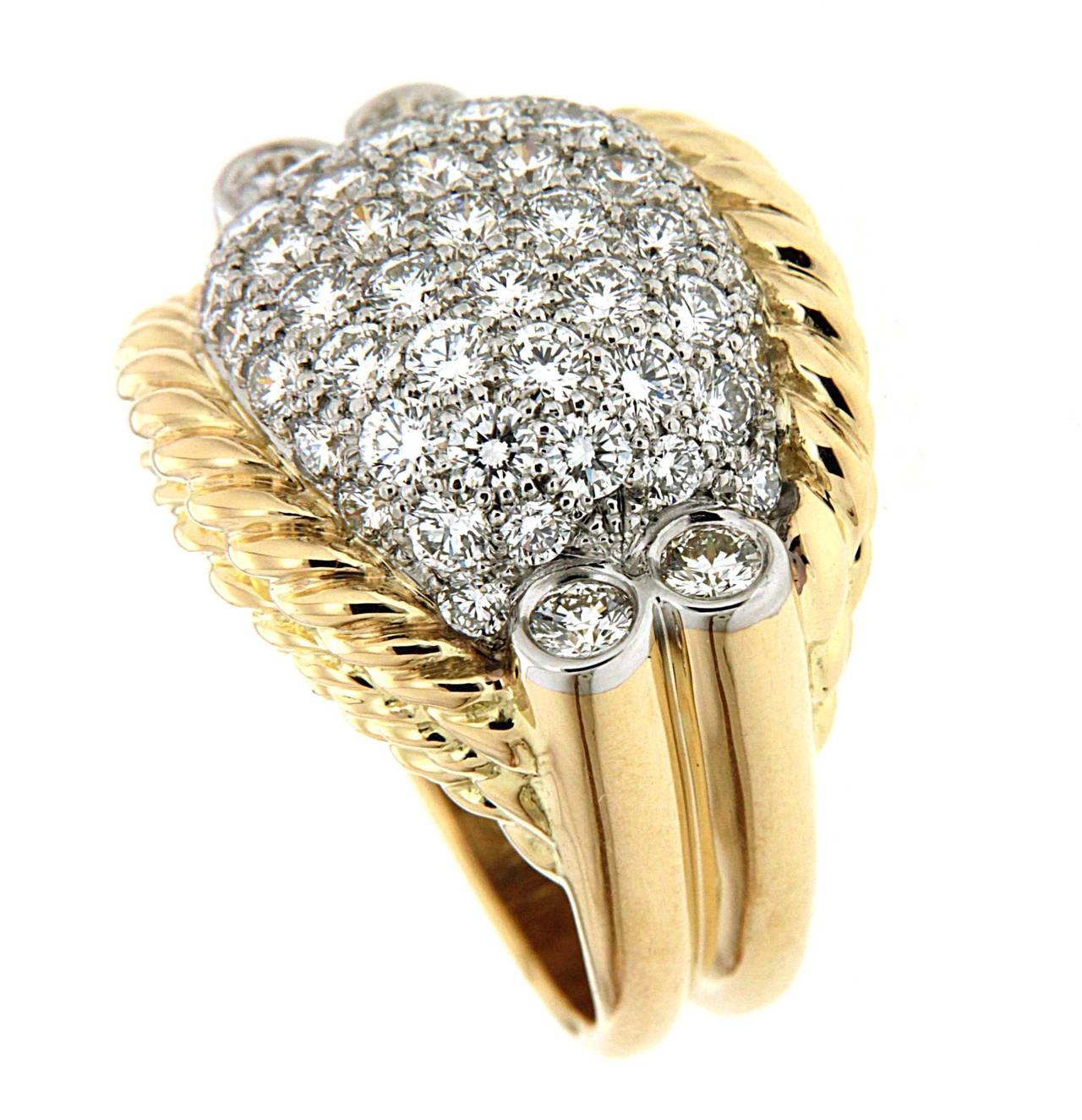 This Triple rope ring is designed with twisted gold wire and pave white diamonds in the center. Four Bezel set Round diamonds on the top of the shanks.This ring is made in 18kt Yellow Gold. 
